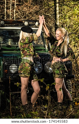Beautiful girls on camouflage outfit, teamwork, off-road vehicle behind - stock photo