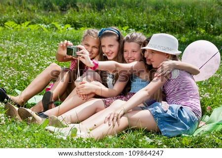 beautiful girls taking picture on grass in city park outdoors - stock photo