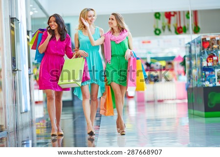 Beautiful girls with paperbags going down the mall - stock photo