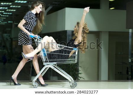 Beautiful girls with sho pping cart - stock photo