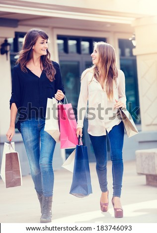 Beautiful girls with shopping bags walking at the mall - stock photo