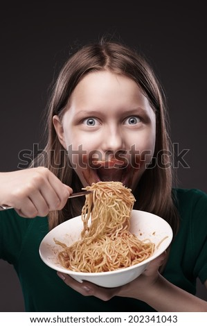 Beautiful glad teen girl greedily eating pasta with sauce on her face - stock photo