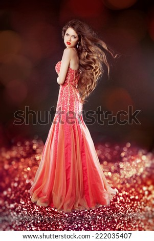 Beautiful glam with long hair posing in red dress over bokeh bright background. - stock photo