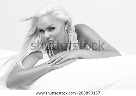 Beautiful glamorous blond woman wearing pearl necklaces and jewellery relaxing on her stomach on a bed looking sideways at the camera with a serious expression, greyscale portrait - stock photo
