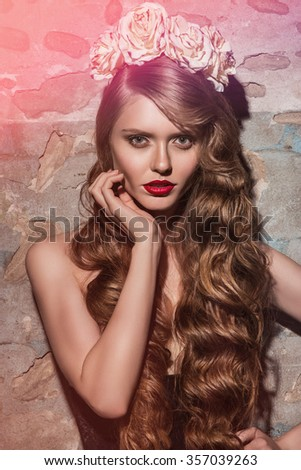 Beautiful glamorous brunette girl with curly long hair. Studio shot. Bright makeup with red lipstick. Beauty. Sexy girl in underwear. With white roses on  head. Closeup portrait. - stock photo