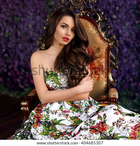 Beautiful glamorous girl in colorful dress sitting in armchair at background full of purple flowers  - stock photo