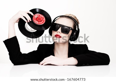 Beautiful glamorous sensual disc jockey wearing sunglasses and headphones and holding two vinyl records in her head, isolated on white - stock photo