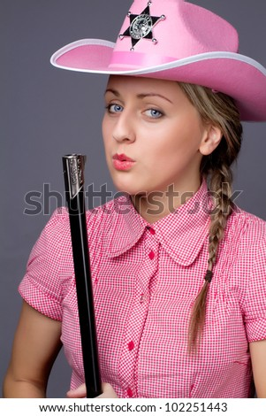 Beautiful glamour cowboy blows on the barrel - stock photo