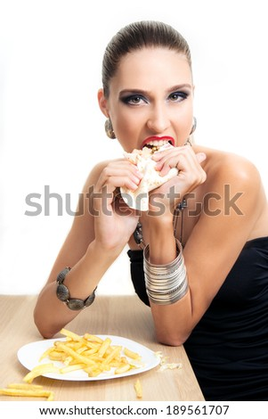 Beautiful glamour woman is eating fast food, fashion style - stock photo