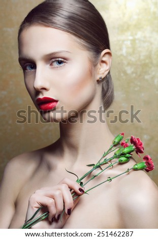 Beautiful glamour woman with perfect professional make up and flowers in her hand. Clean fresh skin. Red provocative lips. - stock photo