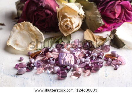 beautiful glass beads on white wooden table with dried roses - stock photo