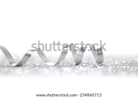 Beautiful glitter silver ribbon tape curl in glitter background - stock photo