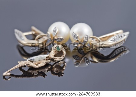 Beautiful gold earrings with pearls and a gold pendant in the form of the Salamander - stock photo