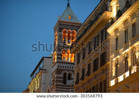 Beautiful golden bells in church tower among illuminated stone historical buildings in evening time on clear blue sky background,  horizontal picture - stock photo