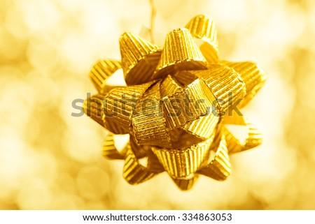 beautiful golden bow on shiny background - stock photo