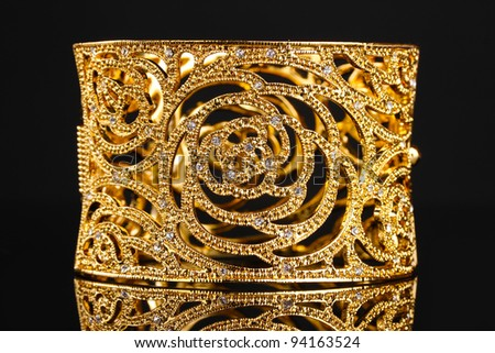beautiful golden bracelet on black background - stock photo