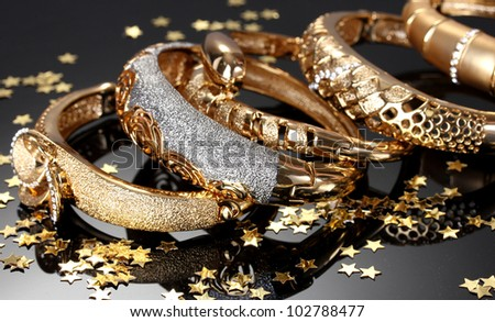 Beautiful golden bracelets on grey background - stock photo