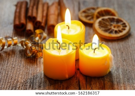 Beautiful golden candles on wooden table.  - stock photo