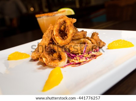 Beautiful golden crispy deep fried calamari rings, served on a white plate, with orange segments and a cocktail out of focus in the background. - stock photo