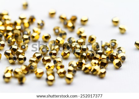 Beautiful golden glass beads closeup on white background - stock photo