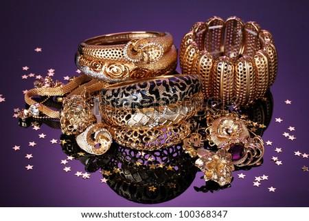 Beautiful golden jewelry on purple background - stock photo
