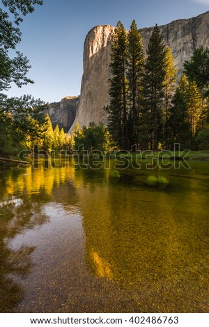 Beautiful golden sunrise on El Capitan with relfection in Merced River. - stock photo