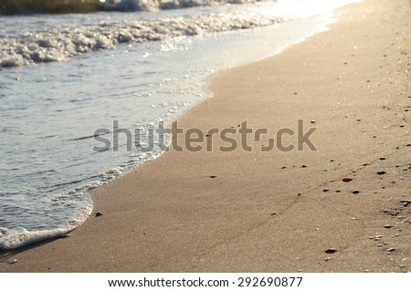 Beautiful golden sunset on the sea shore and textured sand - stock photo