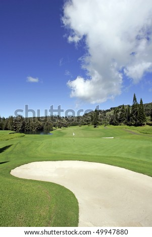 Beautiful Golf Course Fairway with White Sand Bunker, Blue Sky and Dramatic Fluffy Clouds - stock photo