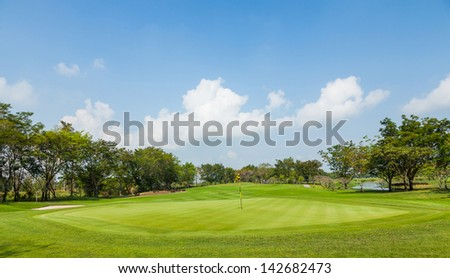 Beautiful golf course green and blue sky in bright sunlight - stock photo