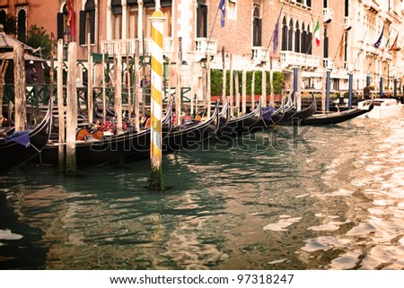 Beautiful gondolas parked in a row on pier of Grand canal in Venice, Italy - stock photo