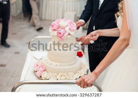 beautiful gorgeous blonde bride and stylish groom cutting colorful cake, celebrating wedding - stock photo