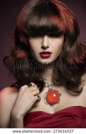 Beautiful, gorgeous, mysterious brunette girl with nice smooth hairstyle with straight fringe, wearing red top and big ol fashioned necklace. - stock photo