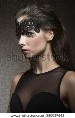 Beautiful, gorgeous, stunning brunette woman with transparent mask on the face, make up is dark with pink lips. She is wearing black transparent top. - stock photo