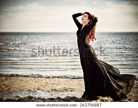 Beautiful goth girl standing on the sea beach - stock photo