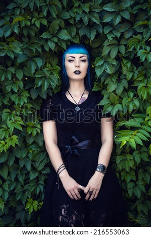 Beautiful goth girl with bright blue hair standing in the green ivy. On the eve of Halloween - stock photo