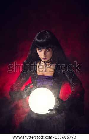 Beautiful gothic style fortune teller with a crystal ball, studio shot over smoky background  - stock photo