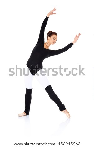 Beautiful graceful ballerina practising her ballet in a black leotard with outstretched arms and leg over a reflective white background - stock photo