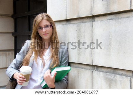 Beautiful grad student with book and coffee - stock photo