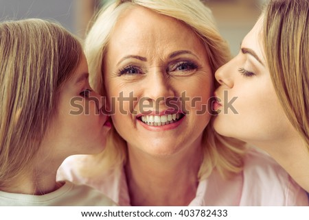 Beautiful granny is looking at camera and smiling while her daughter and granddaughter are kissing her - stock photo
