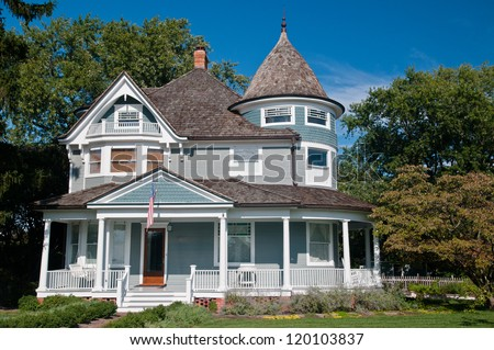 Beautiful gray traditional victorian house.  House has an American Flag hanging over the porch and shows a beautiful garden with flowers and trees.  Set against a cloudless blue sky - stock photo