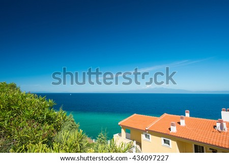 Beautiful Greek coastline with traditional house in the foreground. - stock photo