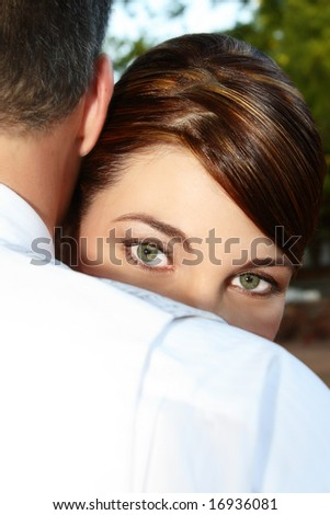 Beautiful green eyes of a bride looking over the grooms shoulder - stock photo