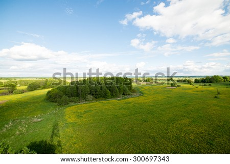 beautiful green fields under blue sky in summer with white clouds and perspective - stock photo