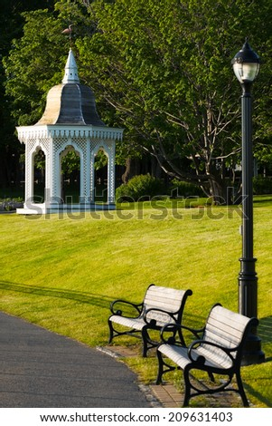 Beautiful green grassy park with a lacy white gazebo, lamppost and garden benches. Popular wedding venue. Location: Bar Harbor, Maine, USA - stock photo