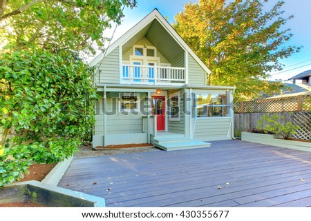 Beautiful green northwest home with wooden porch - stock photo