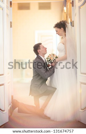 beautiful groom and bride during wedding ceremony in old town hall interior - stock photo