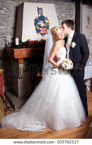 beautiful groom and bride in interior near fireplace on wedding day - stock photo