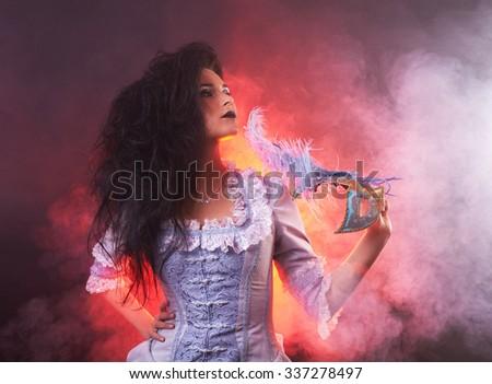 Beautiful Halloween vampire woman aristocrat with venetian mask - stock photo