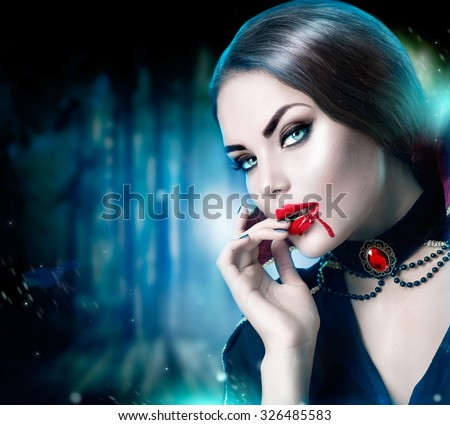 Beautiful Halloween Vampire Woman portrait. Beauty Sexy Vampire lady with blood on her mouth looking at camera. Fashion Art design. Attractive model girl in Halloween costume and make up  - stock photo