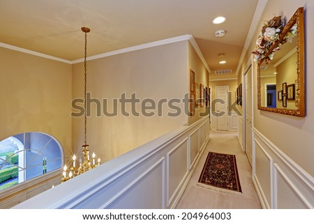 Beautiful hallway in luxury house. Wall decorated with mirror and family pictures - stock photo